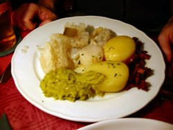Lutefisk (on the upper left side of the plate) as served in a Norwegian restaurant, with potatoes, mashed peas, and bacon