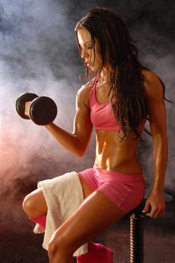 Fitness model posing with dumbbell