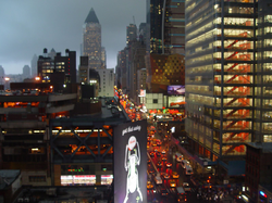 """8th Avenue, looking northward (""""Uptown""""), in the rain. Most streets and avenues in Manhattan's grid plan incorporate a one-way traffic configuration."""