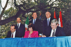 From left to right: (standing) President  Carlos Salinas  , President Bush, Prime Minister  Brian Mulroney  ; (seated)  Jaime Serra Puche  ,  Carla Hills  , and  Michael Wilson  at the NAFTA Initialing Ceremony, October 1992