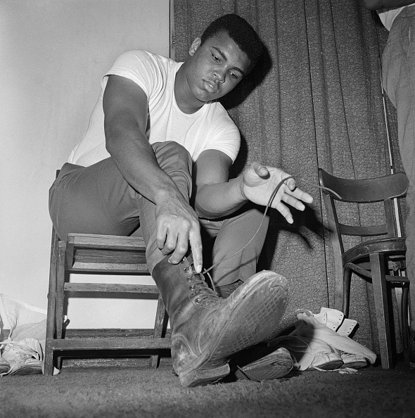Muhammad Ali, shortly after finding out that he will be drafted into the Vietnam War, tries on army boots (Location unspecified. February 1966)