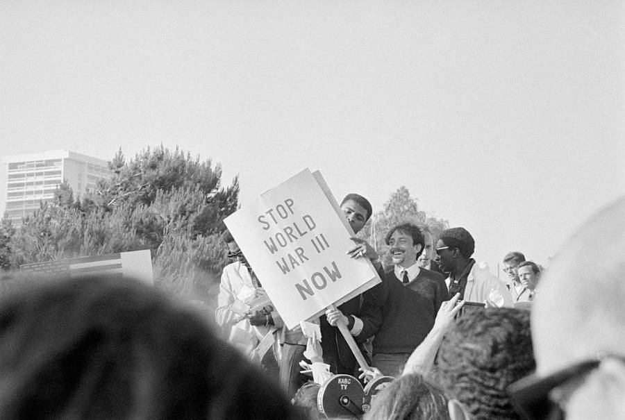 """Muhammad Ali holds up a sign that reads """"Stop World War III Now,"""" joining an anti-war protest outside of President Lyndon B. Johnsonhotel (Los Angeles. June 23, 1967)"""