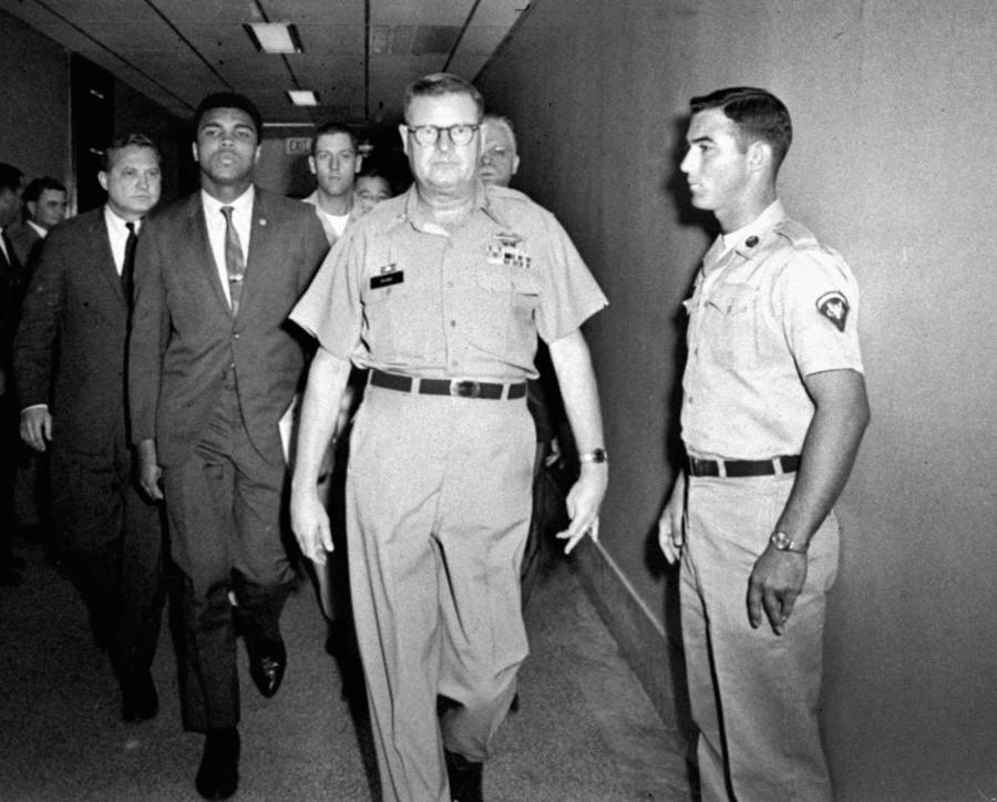 Muhammad Ali is escorted from the Armed Forces Examining and Entrance Station after formally refusing the draft (Houston. April 1967)