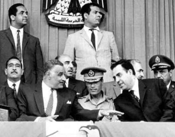 Gaddafi at an Arab summit in Libya in 1969, shortly after the September Revolution that toppled King Idris I. Gaddafi sits in military uniform in the middle, surrounded by President Gamal Abdel Nasser (left) and Syrian President Nureddin al-Atassi (right).