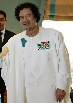Muammar Gaddafi wearing an insignie showing the image of the African continent