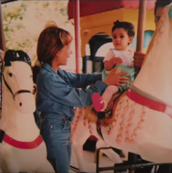 A young Camila Cabello with her mom, Sinuhe Cabello; Camila is riding on a carousel