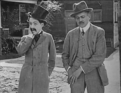 Chaplin (left) in his first film appearance, Making a Living (1914)