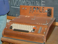 The                                 Apple I                                , Apple's first product, was sold as an assembled circuit board and lacked basic features such as a keyboard, monitor, and case. The owner of this unit added a keyboard and a wooden case.