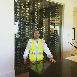 Antik Bose standing in front of the 1000 bottles cellar at his Sammamish Mansion