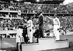 Jesse Owens on the podium after winning the long jump at the                                 1936 Summer Olympics                                .