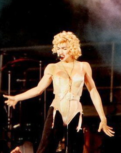 "Madonna using the ""Madonna mic"" during the 1990                                 Blond Ambition World Tour                                . She was one of the earliest adopters of hands-free headsets."