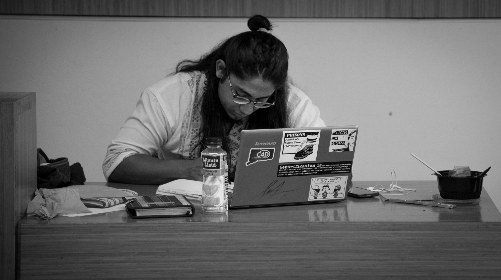 Black and white photo of Eric working on his laptop.