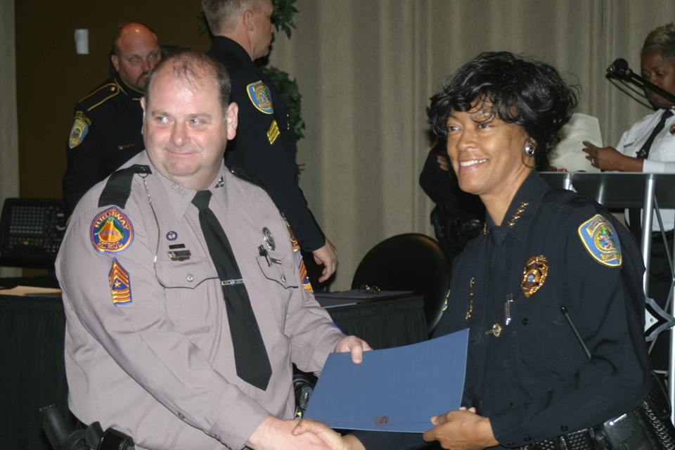 Photo of Master Sergeant William Trampass Bishop receiving an award from Chief Gilmore for catching a hit and run driver.