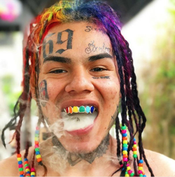 Teka$hi69's rainbow hair and grill
