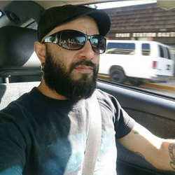 Photo of Carlos while he's driving inside of a vehicle.