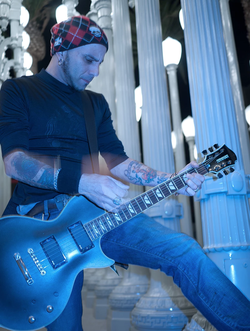Photo of Carlos where he plays his electric guitar at theLACMAurban lights. 