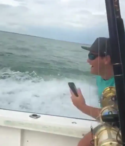 Spencer recording while him and his friends drag the shark behind their boat