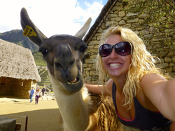 Sarah smiling next to a       Llama      