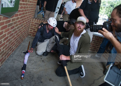 Photo of Josh where he sits near the curb helping a fellow white supremacist comrade.