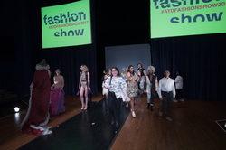 A picture of Droxity and other designers at the end of the show taken by Michigan State University's College of Arts and Letters. (Droxity's design is the colorful one behind him)