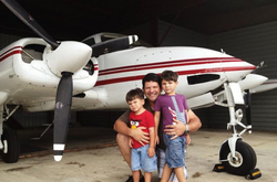 Photo of Julio and two of his children in front of his       Cessna 310                     [2]               