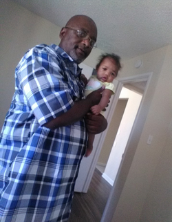 Photo of Fred Lowe holding a little toddler.