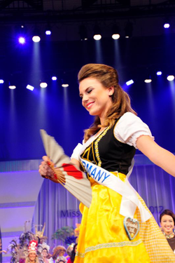 Aline Marie Massel wearing traditional German clothes at the                               Miss International 2012                              ​ pageant after winning the                               Miss International Germany                              pageant