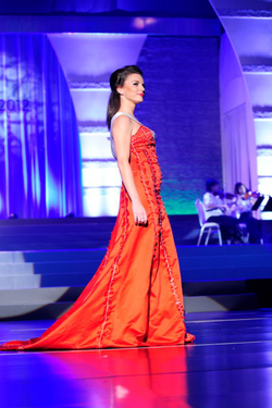 Aline Marie Massel wearing a red dress at the                               Miss International 2012                              ​ pageant after winning the                               Miss International Germany                              pageant