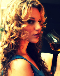 Photo of Aline Marie Massel drinking a beverage out of a                               wine glass                              ​
