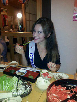 Photo of Aline Marie Massel eating sushi while wearing her                               Miss International Germany                              ​ 2011 sash