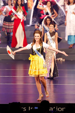 Photo of Aline Marie Massel in traditional German dress at the                               Miss International 2011                              ​ pageant after winning                               Miss International Germany                              ​