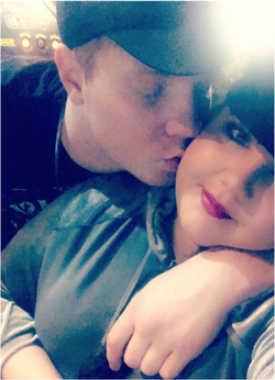 Photo of Danni Tamburo being kissed by her boyfriend, Adam Hicks​.