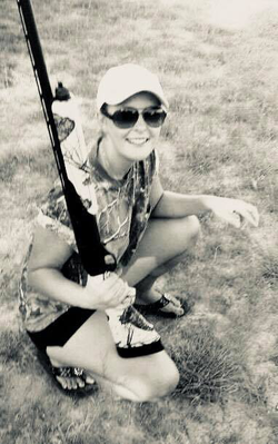 Melissa Shelton squatting with a hunting rifle​.