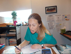 Melissa Bonkoski pulling a funny face at her teacher's desk [8]​