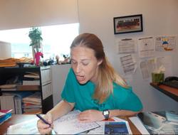 Melissa Bonkoski pulling a funny face at her teacher's desk                                                                  [8]                                                               