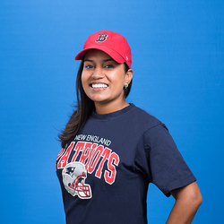 Payal Agrawal Divakarin wearing a Boston Red Sox hat and a New England Patriots shirt in support of her favorite sports teams