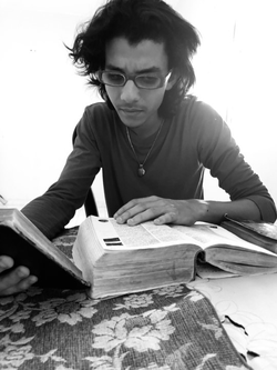 Emil Cerda reading the Bible, Little Larousse (dictionary given by his mother) and Larousse Antonyms and Synonyms. He says he spends reading these three books every day of his life. Photo taken by Juan Miguel Peña.