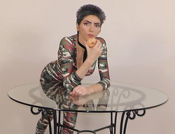 Nasim leaning over a table with a doughnut