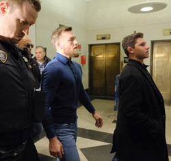 Photo of Casey Judelson walking with Conor McGregor​ inside of the precinct.
