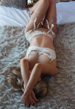 Sarah Louise McGill lying on a bed in lingerie​ [15]​