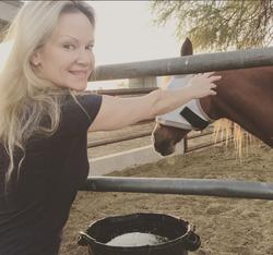 Barbara Moore feeding a horse.