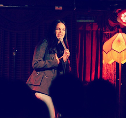 Photo of Edi Gibson performing stand up comedy. [13]​