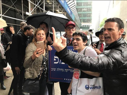 Aaron M. Schlossberg showing the middle finger to his nemesis at a rally.