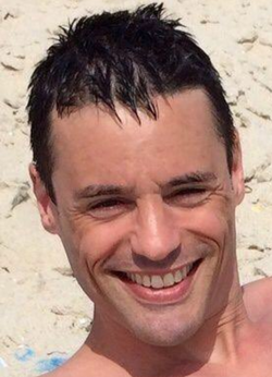 Photo of Aaron M. Schlossberg laying in the sand.