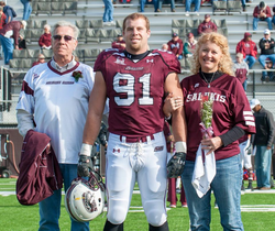 Jason Seaman in his Southern Illinois Salukis Football Team​ uniform with his parents [3]​