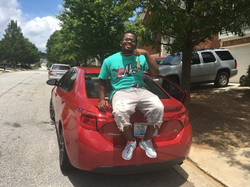 Photo of Dedrick Williams sitting on a Toyota Corolla​ [7]​