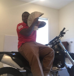 Photo of Dedrick Williams showing off some cash while sitting on a dirt bike​ [7]​