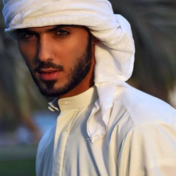 Omar Borkan wearing a traditional white thobe and a keffiyah