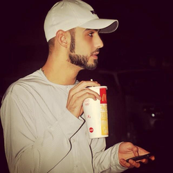 Omar Borkan with a drink from McDonald's​, wearing a gray thobe and a French-styled chin-strap beard