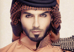 Omar Borkan wearing a brown embroided thobe